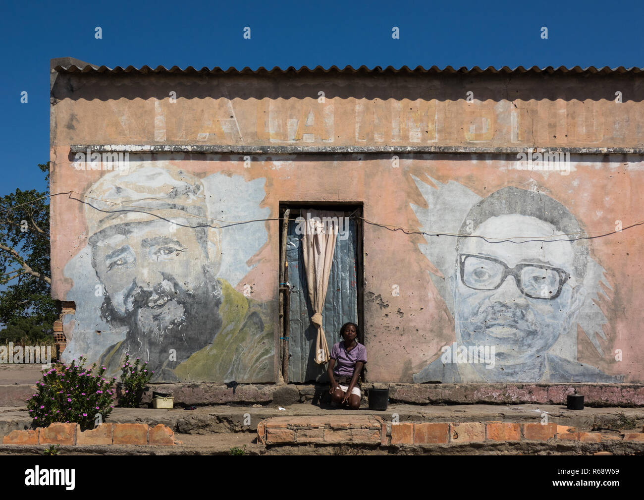 Young woman in front of her house with an old Communist propaganda wall painting of Fidel Castro and Agostinho Neto, Huila Province, Vilhambundu, Ango - Stock Image