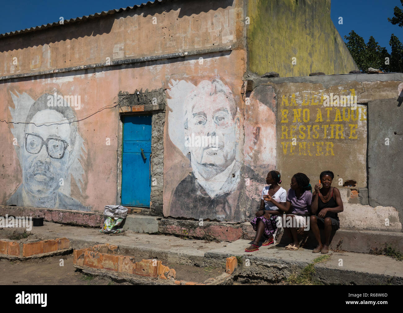 Young women in front of her house with an old Communist propaganda wall painting of Leonid Brejnev and Agostinho Neto, Huila Province, Vilhambundu, An - Stock Image