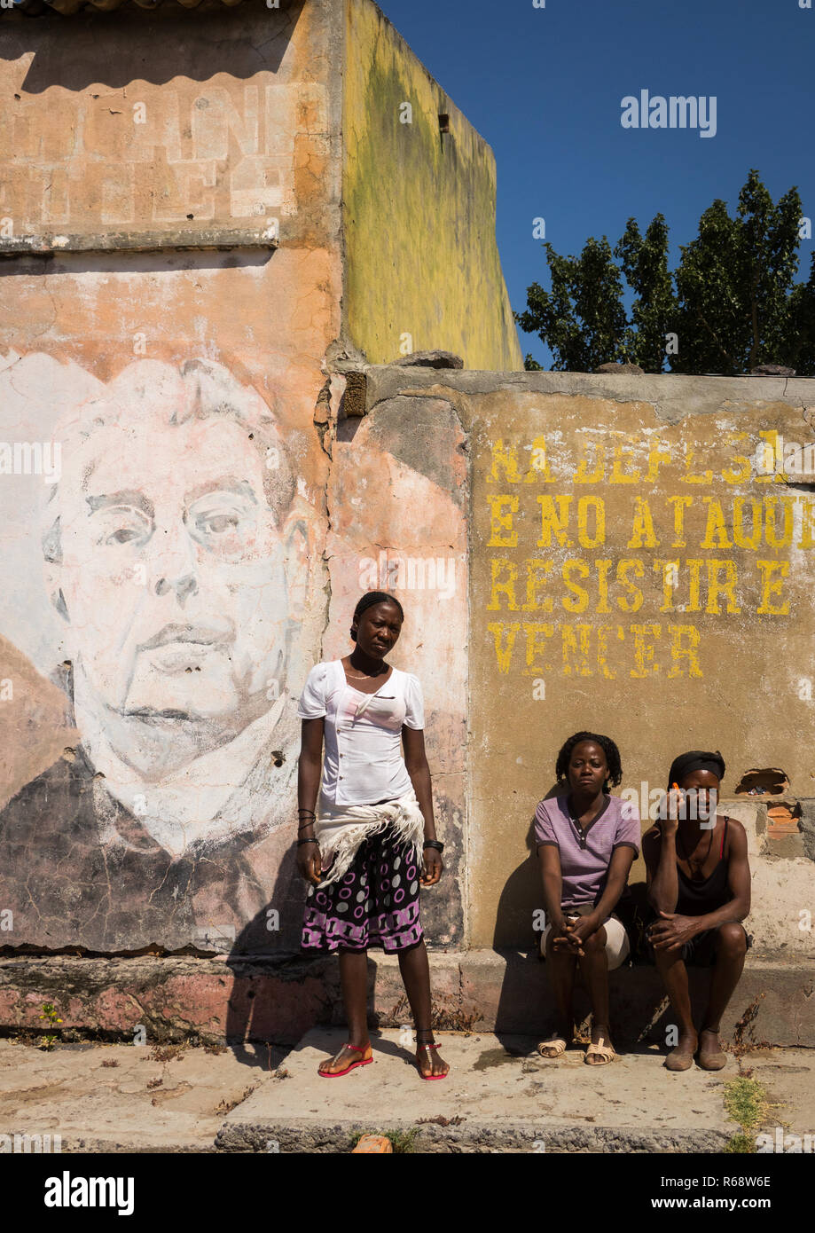 Young women in front of her house with an old Communist propaganda wall painting of Leonid Brejnev, Huila Province, Vilhambundu, Angola - Stock Image