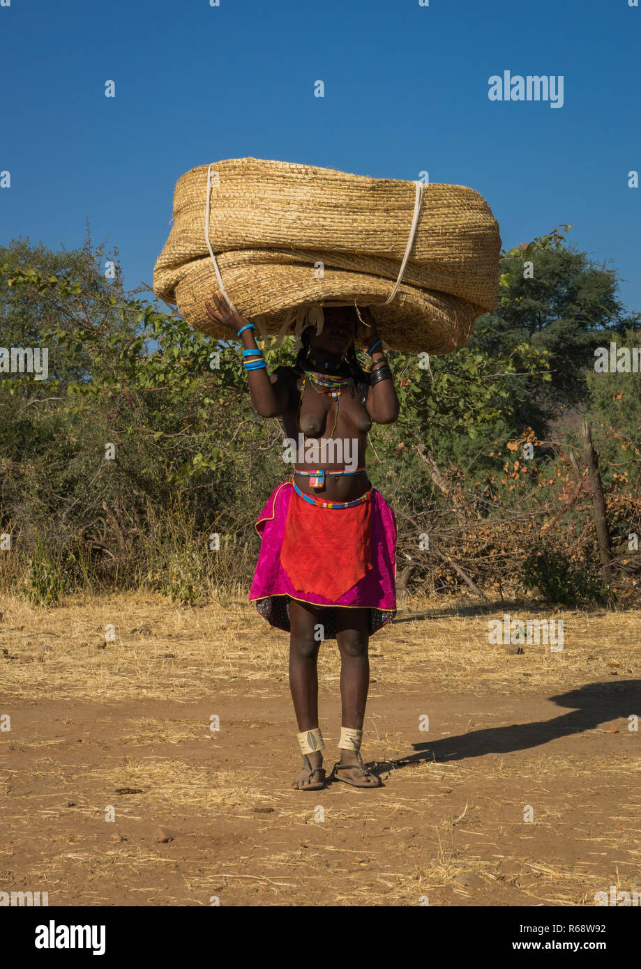 Muhakaona tribe woman carrying a basket on her head, Cunene Province, Oncocua, Angola - Stock Image