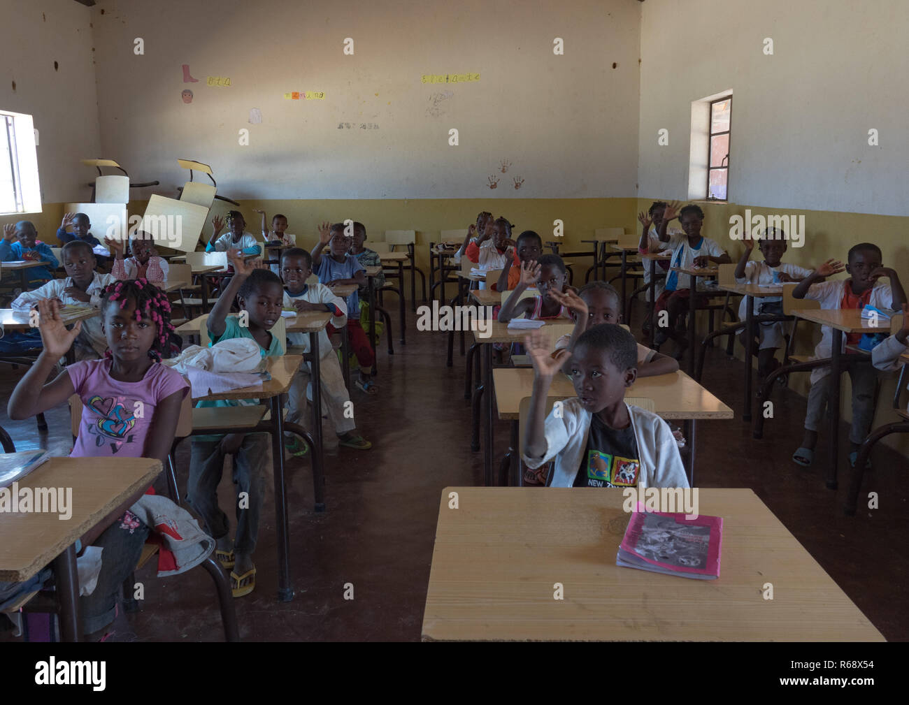 Children in a school waving their hand to welcome visitors, Namibe Province, Caraculo, Angola - Stock Image
