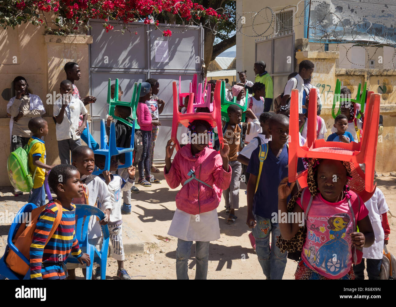 Children going to school with their own chairs, as there are not enough seats for all kids, Huila Province, Lubango, Angola - Stock Image