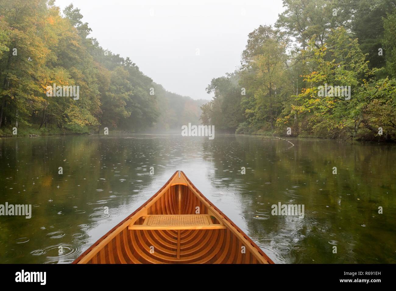 Bow of a cedar canoe on a river during a light rain - Ontario, Canada - Stock Image