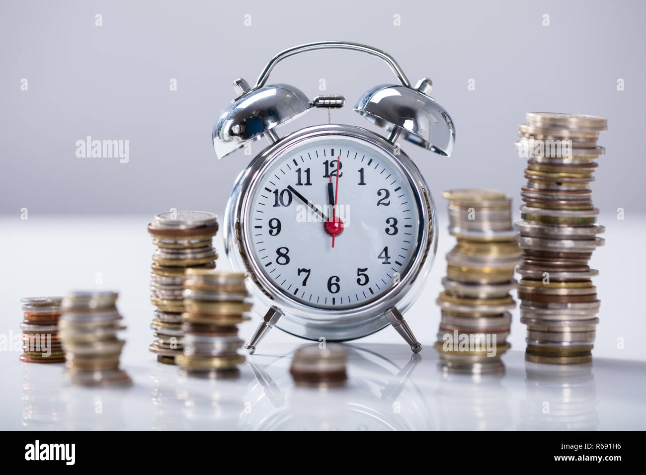 Alarm Clock With Stack Of Coins - Stock Image