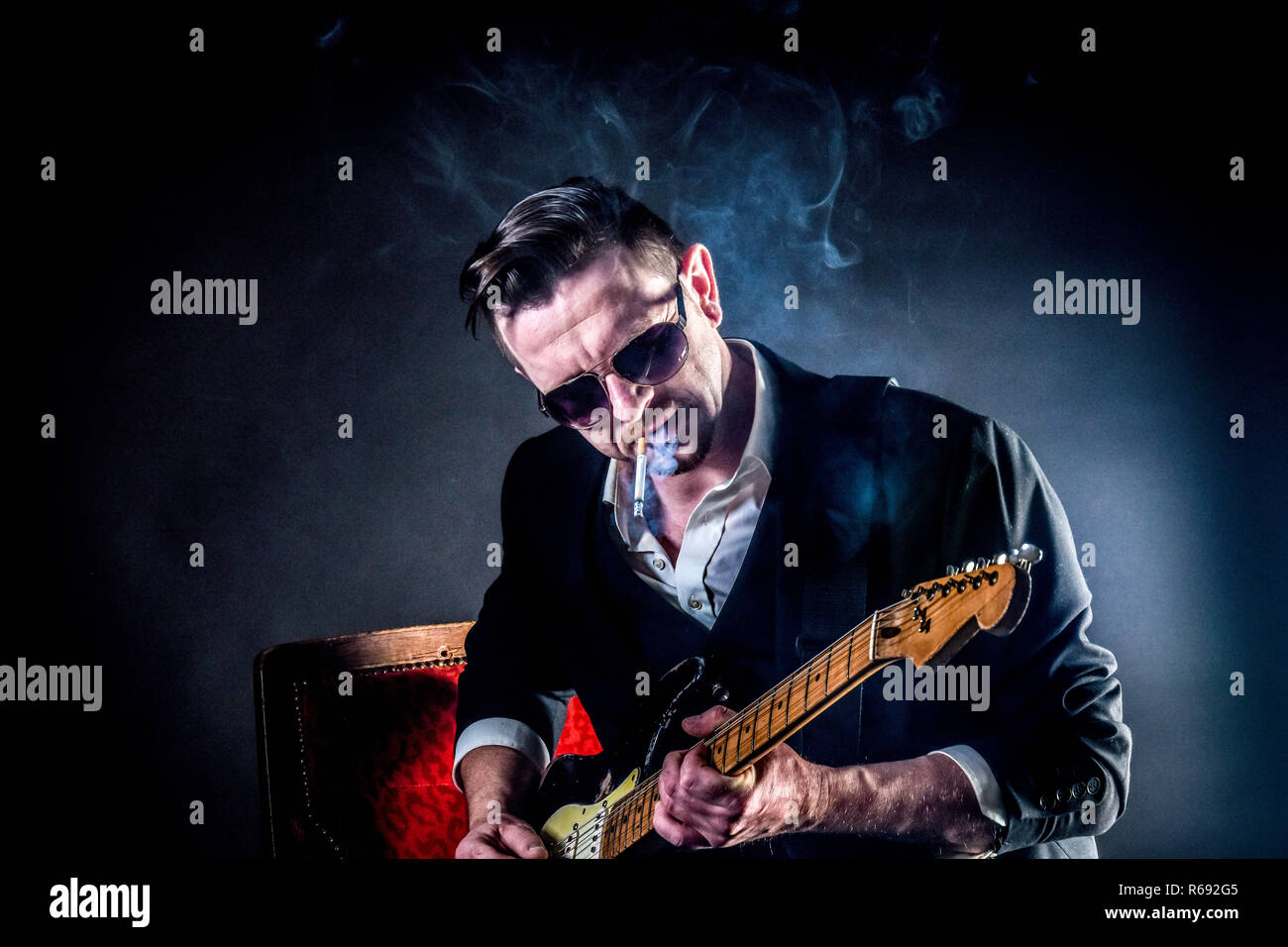 Cool Musician Plays On A Guitar Ans Smokes A Cigarette - Stock Image