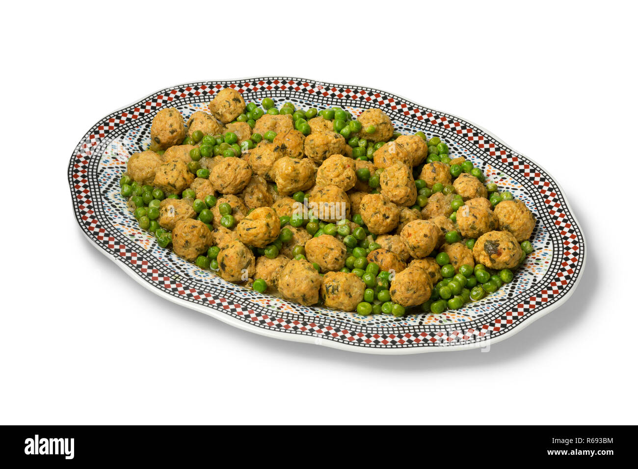 Dish with Moroccan style minced chicken balls and green peas isolated on white background - Stock Image
