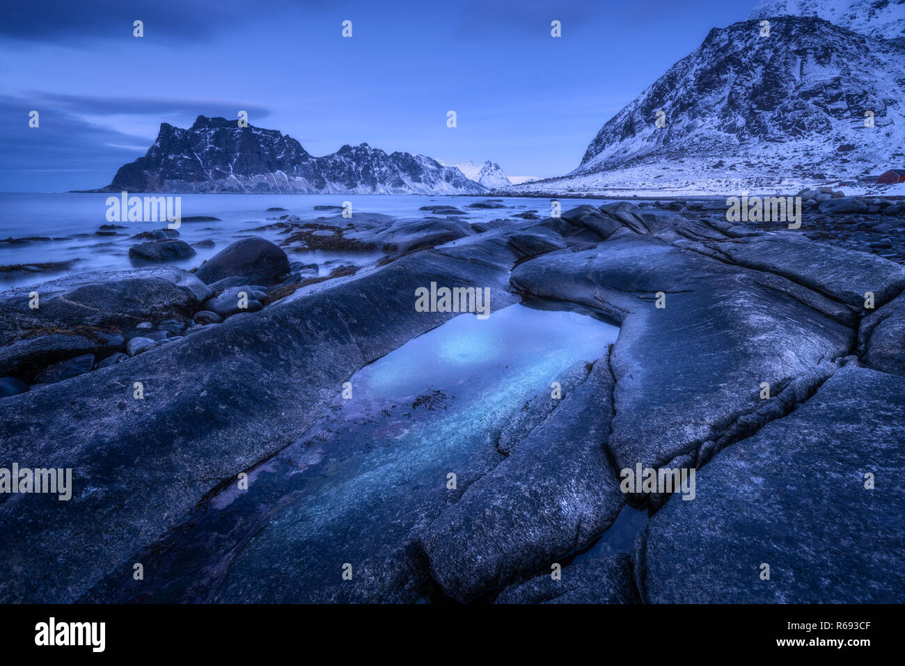 Seashore with stones and blurred water, against snowy mountains and blue sky with clouds at dusk. Uttakleiv beach in Lofoten islands, Norway. Winter l - Stock Image