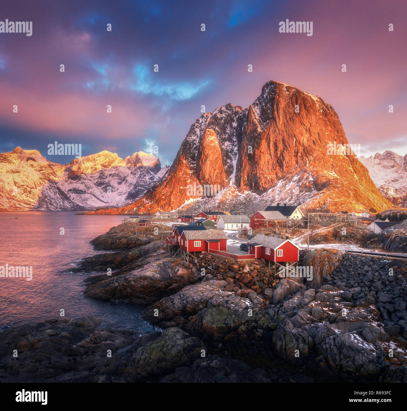 Hamnoy village on the hill at sunrise. Lofoten islands, Norway. Winter landscape with houses, snowy mountains, sea, colorful sky with clouds. Norwegia - Stock Image