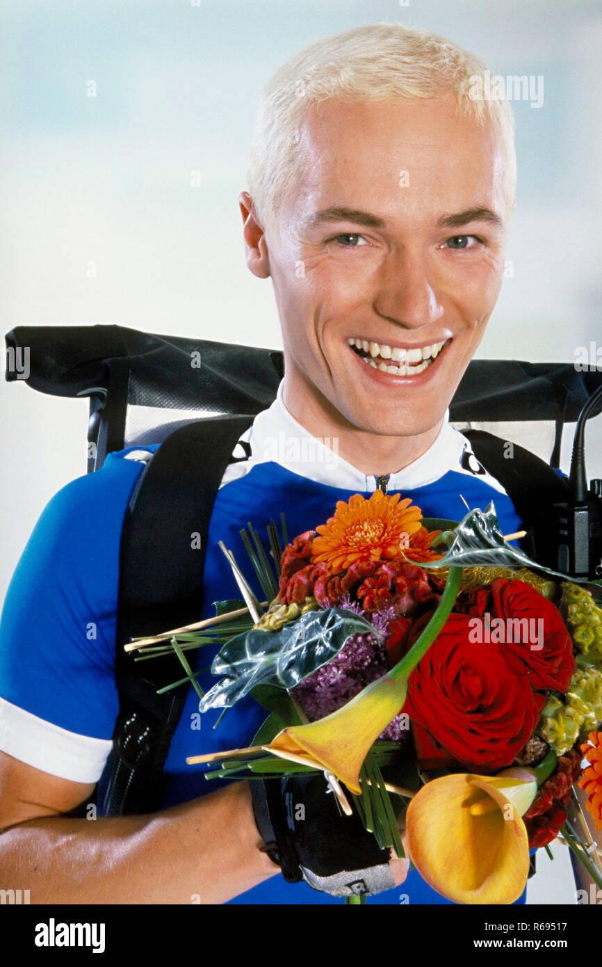 Portrait, Innenraum, laechelnder ca. 30 Jahre alter blonder Fahrradkurier mit einem Blumenstrauss in der Hand Stock Photo