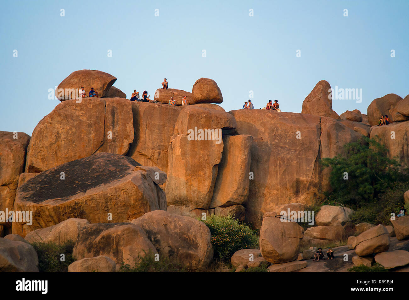 Western tourists and back packers socialise and enjoy a sunset from on top of a large boulder and red rock formation in Hampi, India. - Stock Image