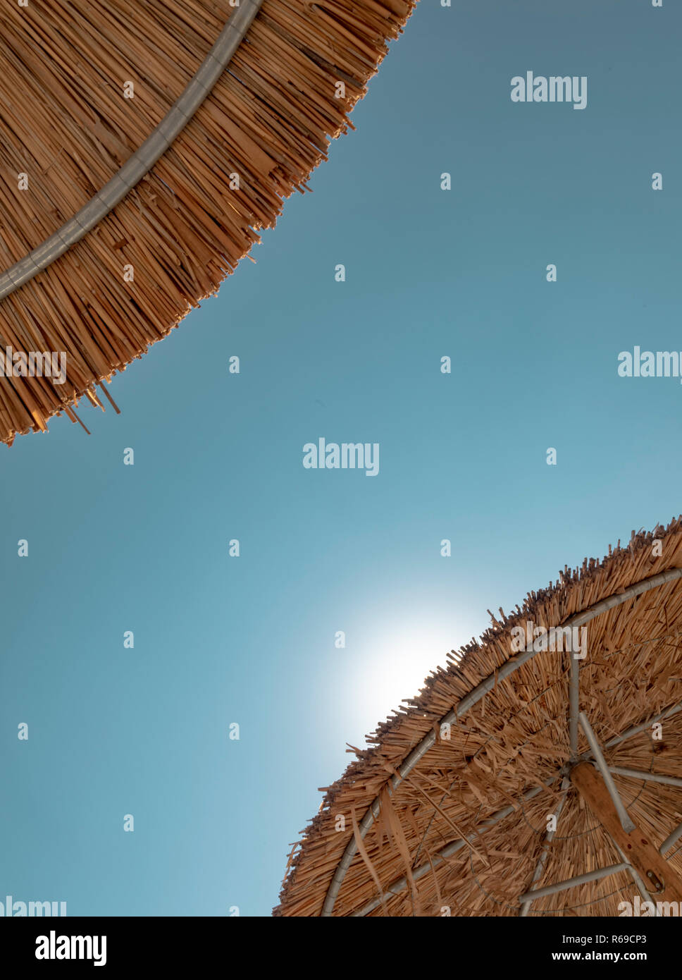 Shot from below of two beach umbrellas made of straw with the sun peaking out from one of them. - Stock Image
