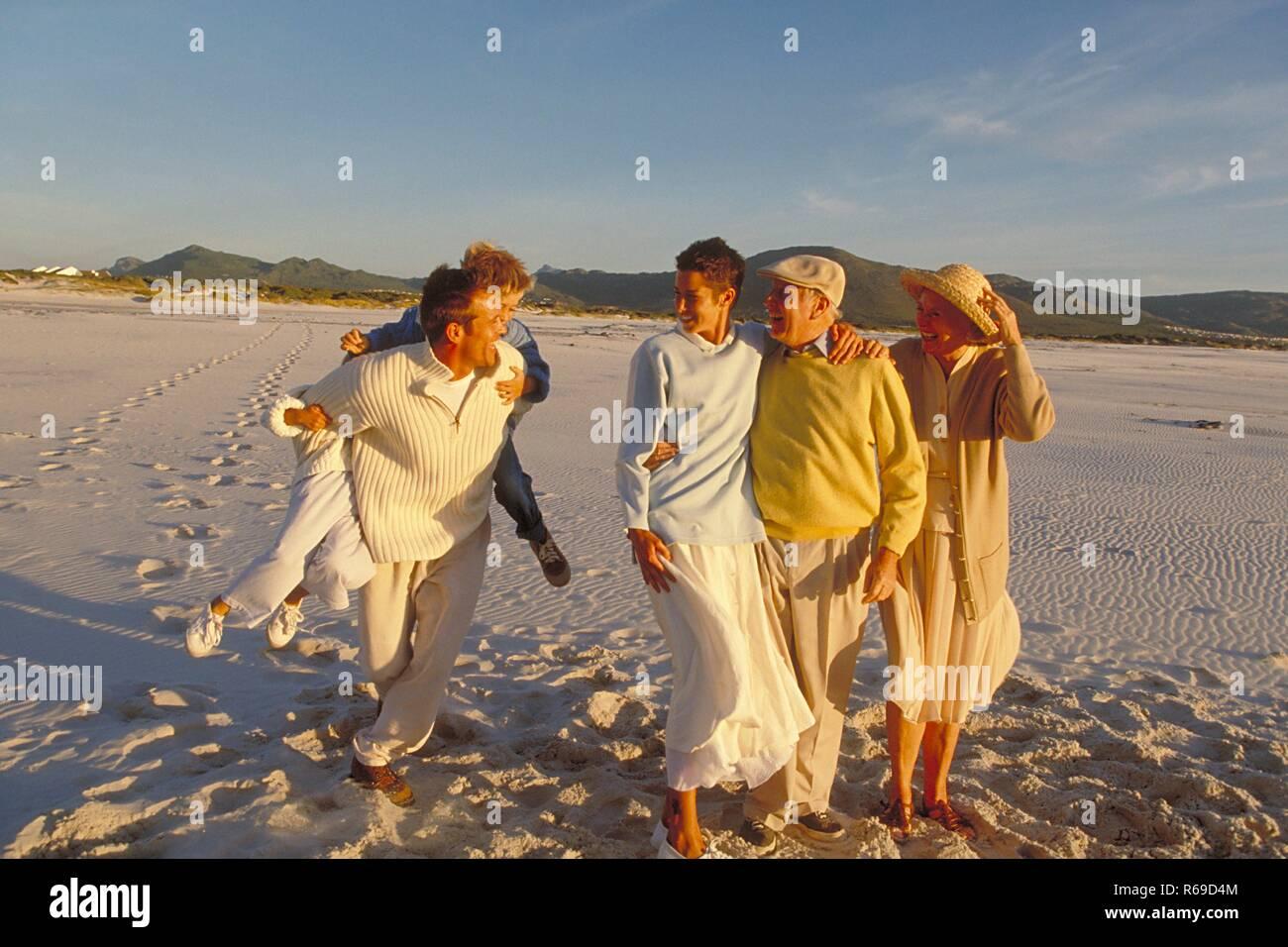 Ganzfigur, 3 Generationen einer Familie gehen am Strand spazieren - Stock Image