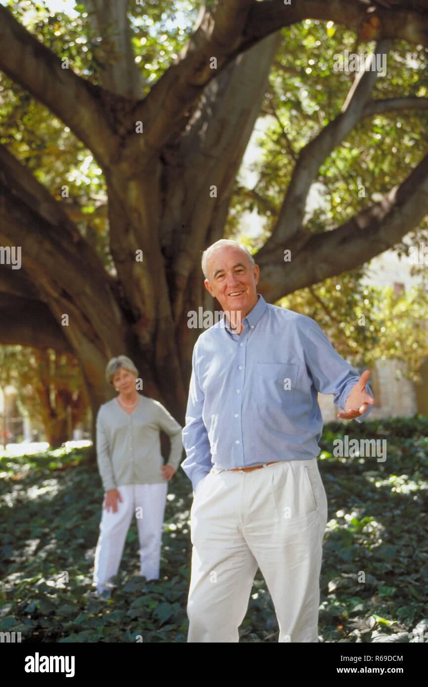 Portrait, Ganzfigur, hell gekleidetes Seniorenpaar steht im Sommer unter einem Baum - Stock Image