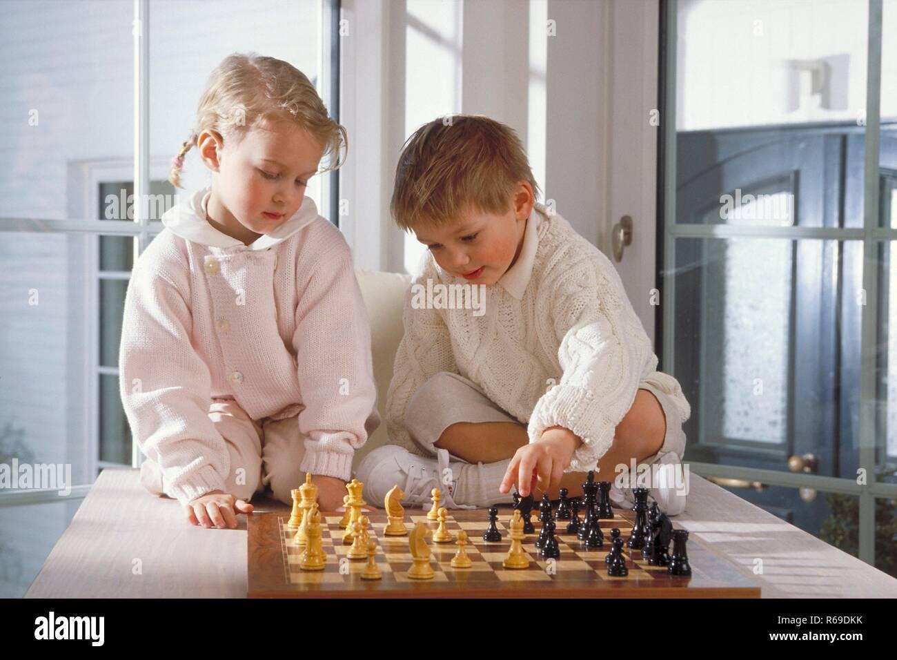 Portrait, Innenraum, Ganzfigur, blondes Maedchen und Junge, 4-5 Jahre alt, beide hell gekleidet, sitzen  auf dem Tisch und spielen Schach Stock Photo