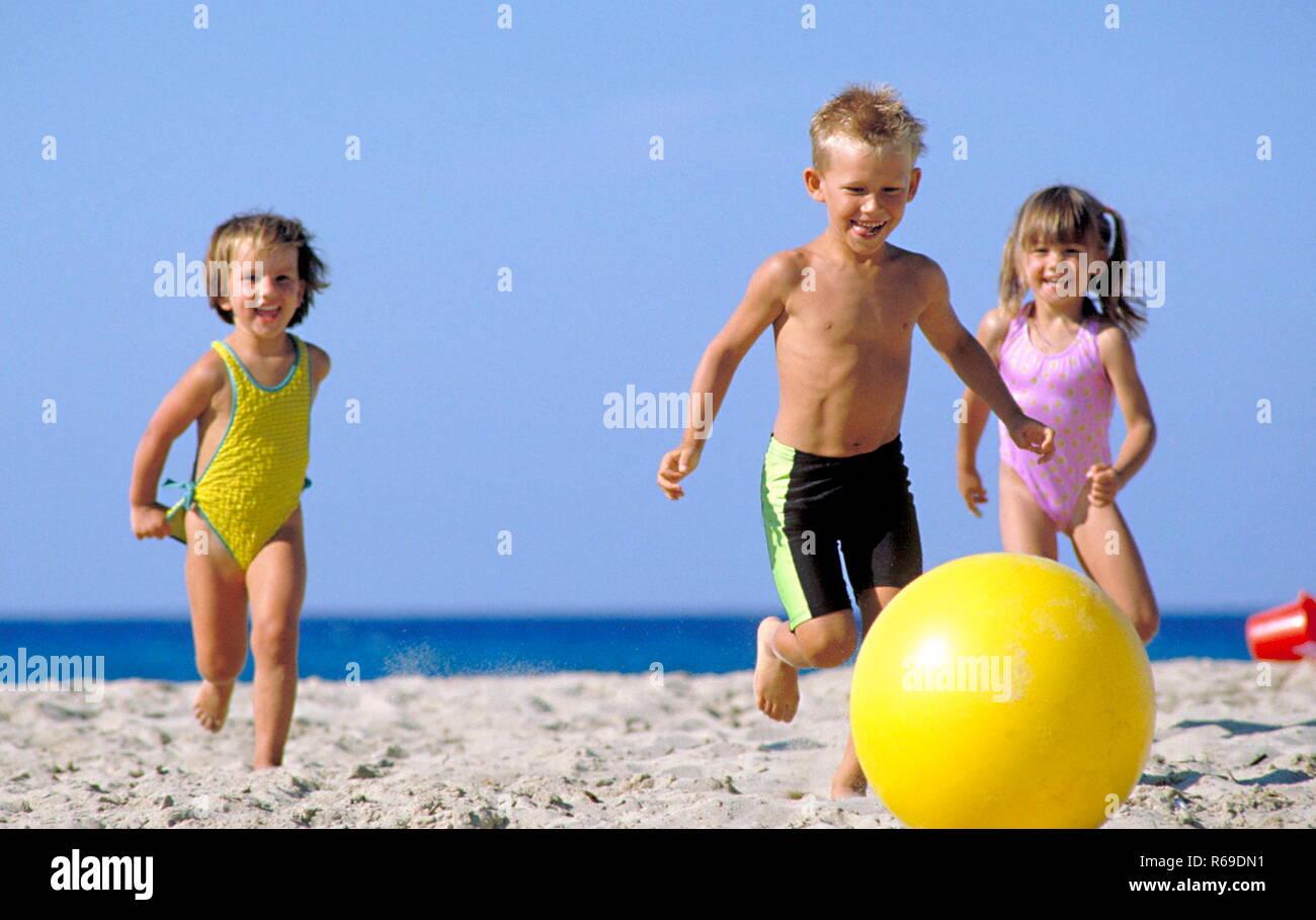 3 kleine Kinder spielen mit einem grossen gelben Ball am Strand - Stock Image