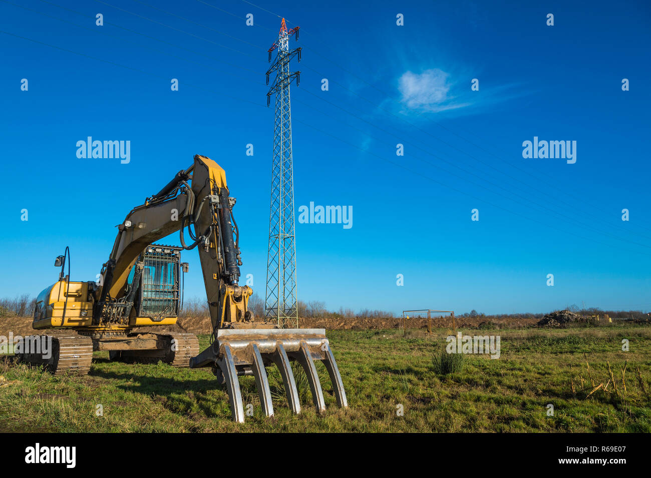Specialty Excavator With Fork For Clearing Of Tree Trunks In Front Of A Pylon. - Stock Image
