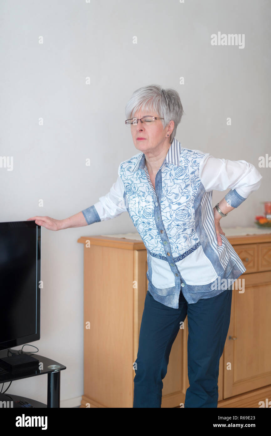 One Senior Has Back Pain And Is Based On The Television On. - Stock Image