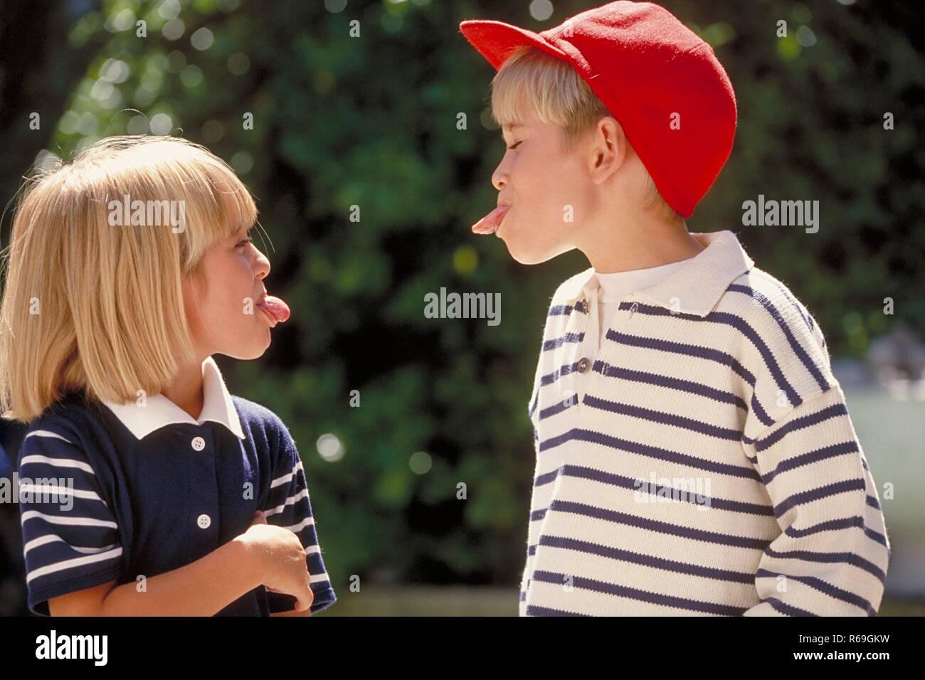 Outdoor, Halbfigur, blau-weiss gekleidetes blondes Kinderpaar, 5-6 Jahre, Junge mit roter Baseballkappe und Maedchen strecken sich gegenseitig die Zunge heraus - Stock Image