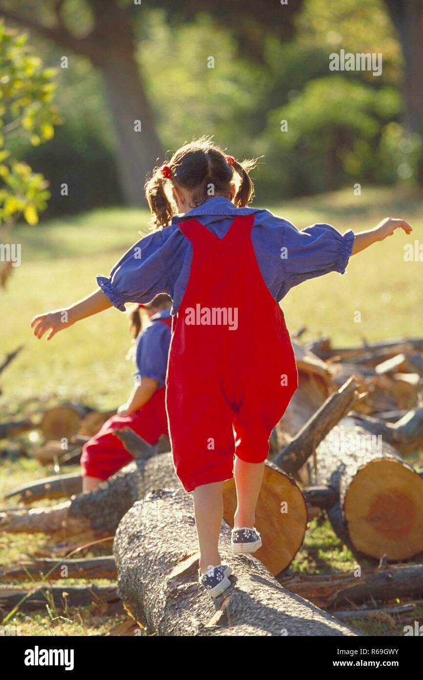 Parkszene, Ganzfigur, 2 bruenette Zwillings-Maedchen, 6 Jahre alt, bekleidet mit roter Latzhose, blauer Bluse und Turnschuhen balancieren ueber dicke Baumstaemme Stock Photo