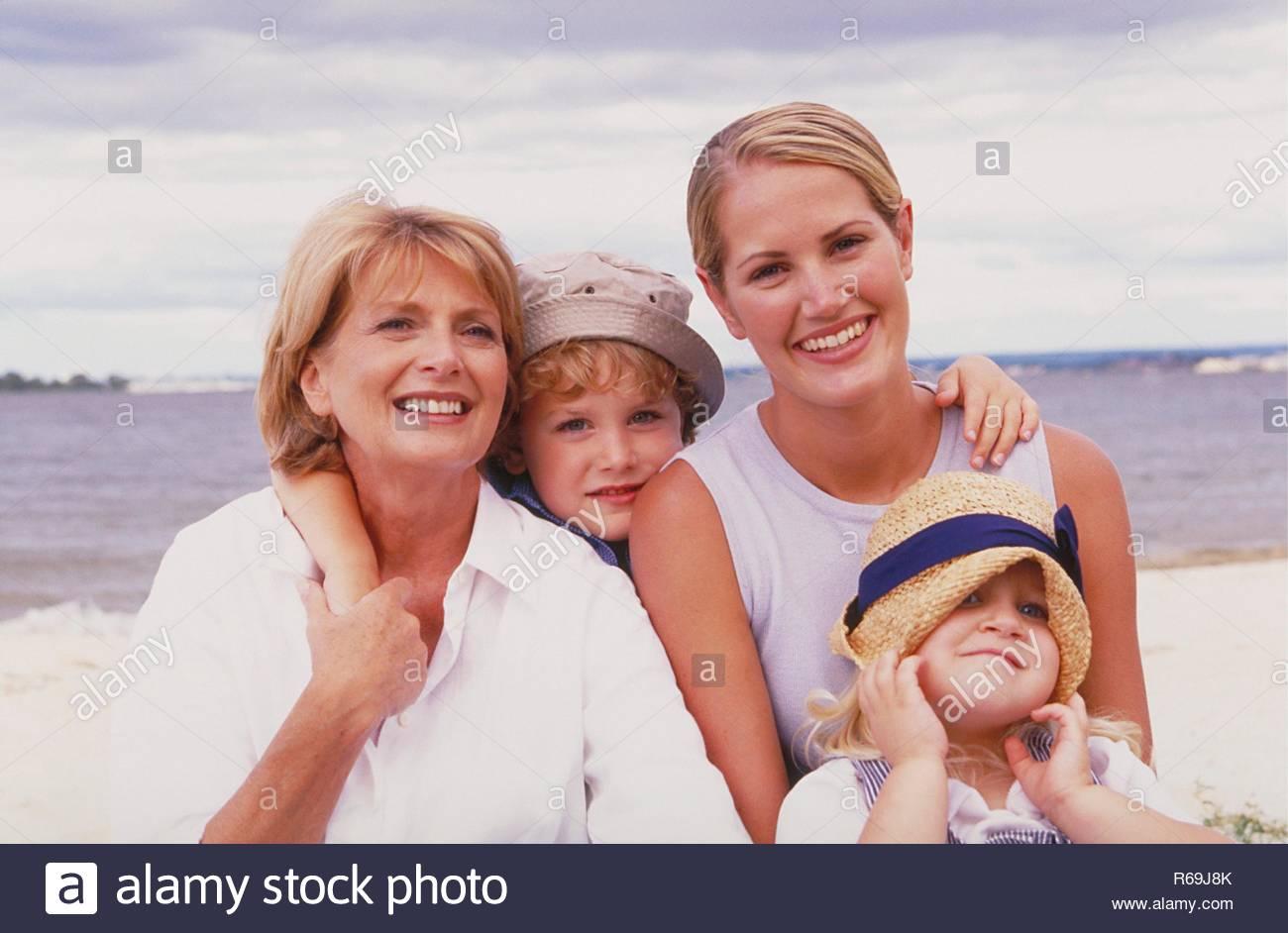 Strand, Portrait, Gruppenbild, 3 Generationen, rotblonde Frau, 50 Jahre, blonde Tochter, 25 Jahre, zwei Kinder, blondes Maedchen, 4 Jahre, mit gestreiftem Kleid und Strohhut und rotblonder Junge, 5 Jahre, mit kariertem Hemd und Sonnenhut am Wasser - Stock Image