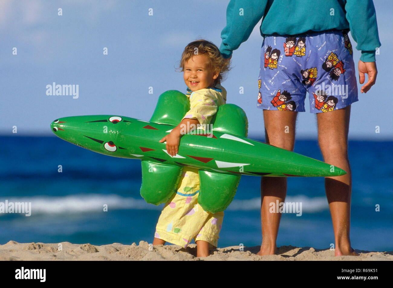 Portrait, Strandszene, Vater geht mit seiner 3 Jahre alten Tochter, die ein grosses Plastikkrokodil unter dem Arm traegt, am Strand spazieren - Stock Image