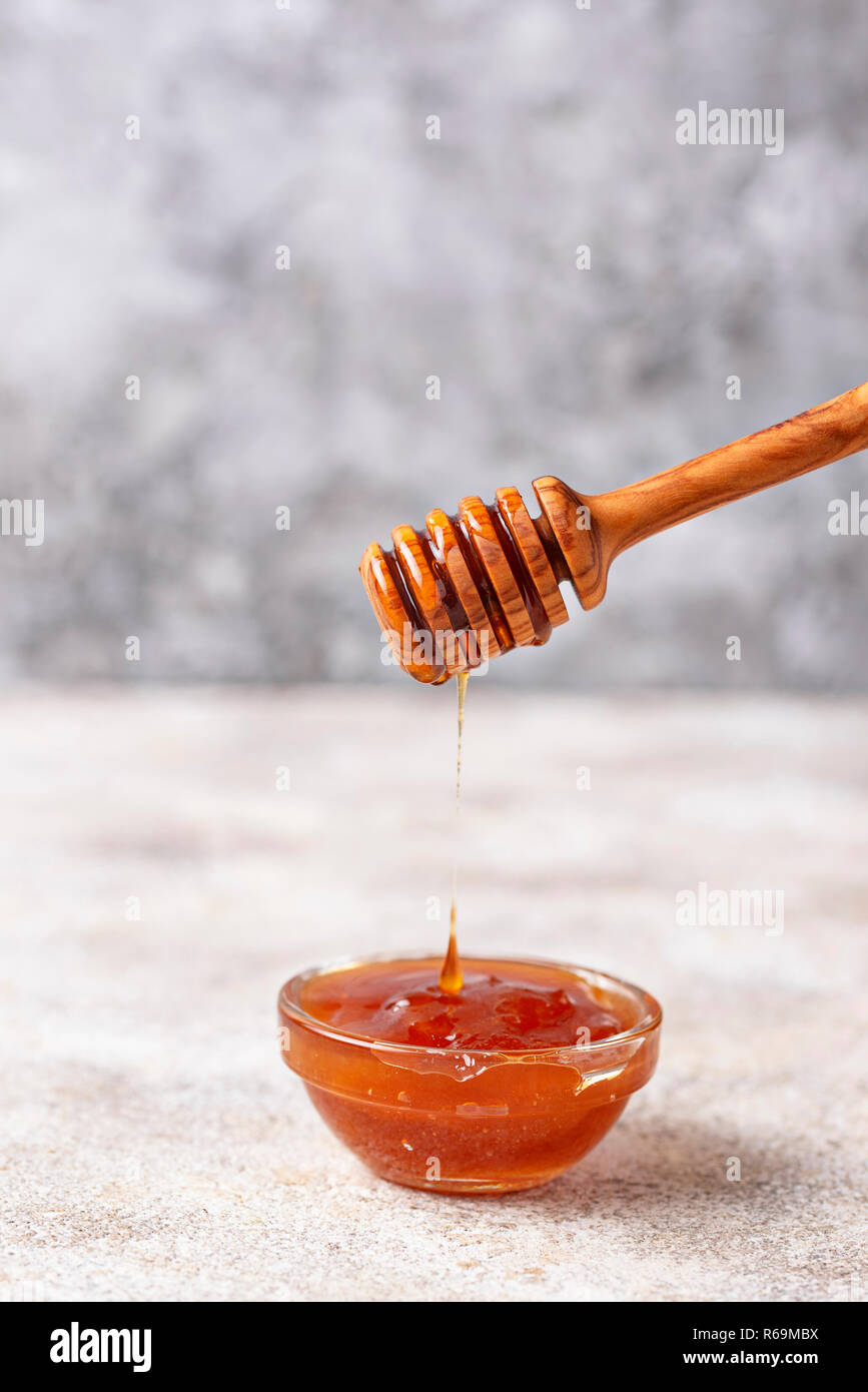 Honey dripping from a wooden dipper - Stock Image