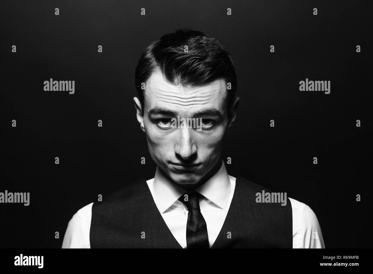 Close up black and white portrait of a young man in a white shirt, black tie and vest, seriously looking at the camera, against plain studio backgroun - Stock Image