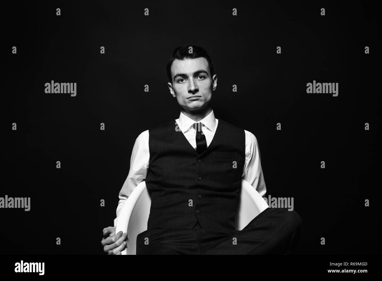 Close up black and white portrait of a young man in a white shirt, black tie and vest, sitting and seriously looking at the camera, against plain stud - Stock Image