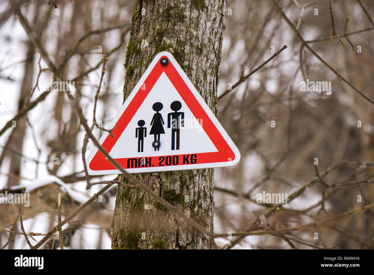 Warning sign of maximum weight 200 kg allowed on wooden bridge at hiking trails in mountain valley in winter. Shape of triangle. - Stock Image