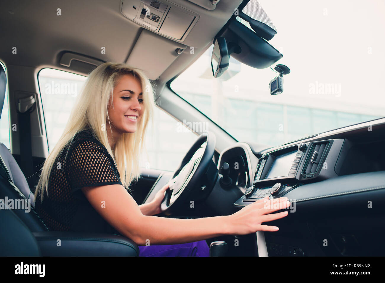 Happy smiling female rejoicing in new expensive purchase in auto showroom. Beautiful customer sitting on door of white folding top car. - Stock Image