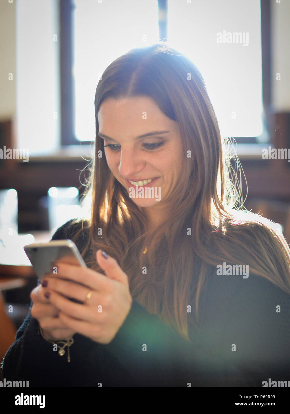 Young woman with smartphone, laughs, Portrait, Café, Stuttgart, Baden-Württemberg, Germany - Stock Image