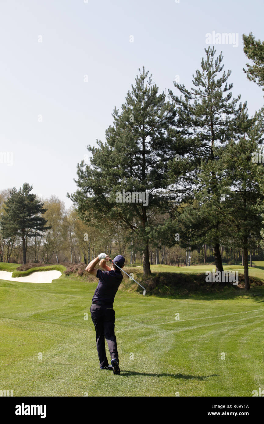 Golfer playing a skilful approach shot over trees to a distant green - Stock Image
