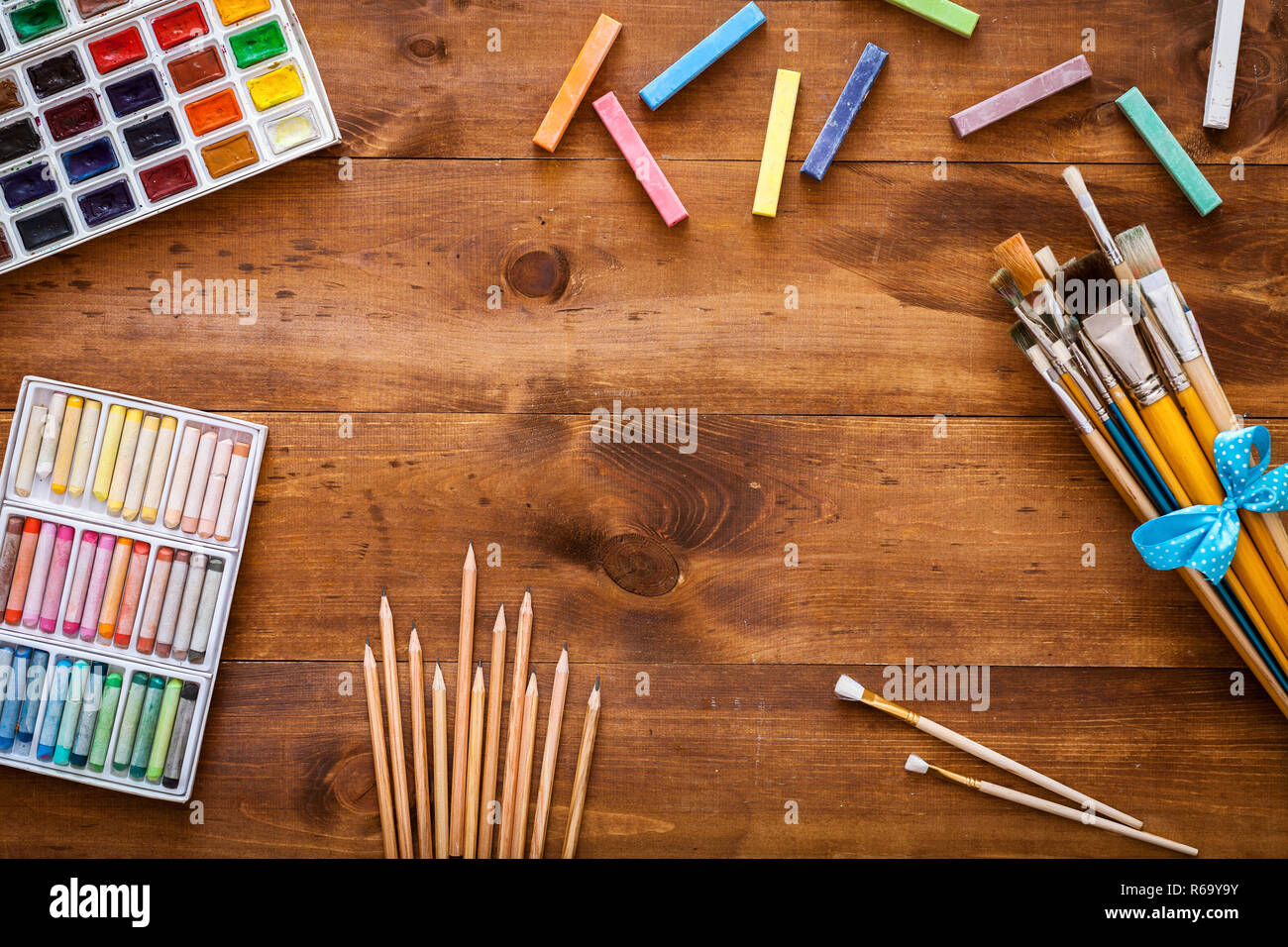 Creative art work accessories tools supplies set on messy desk, paint brushes, paintbox watercolors crayons pencils on brown wooden artistic backgroun - Stock Image