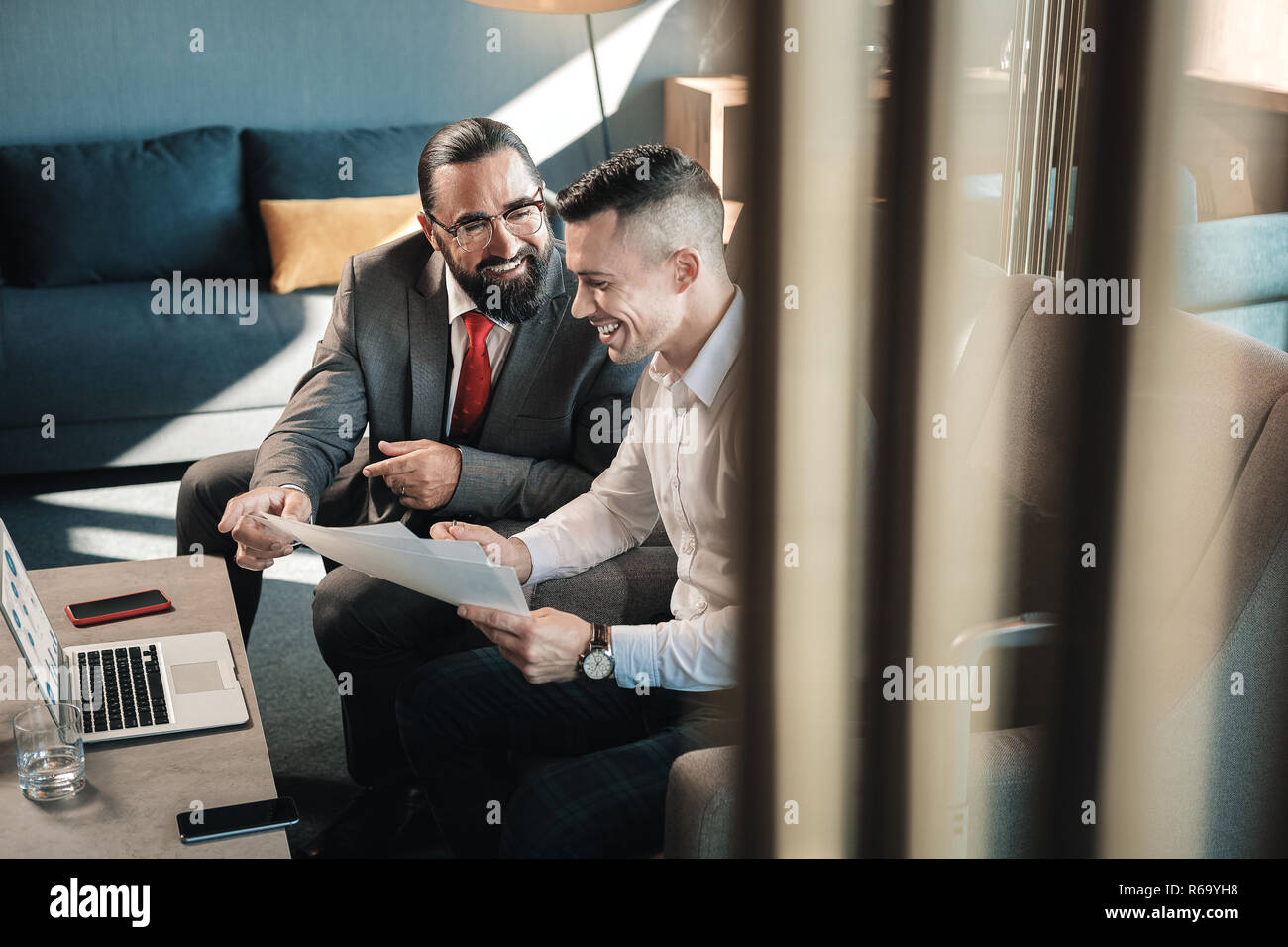 Two prosperous business partners laughing while communicating - Stock Image
