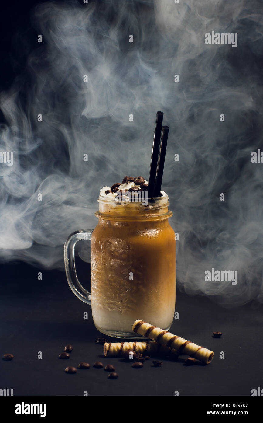 Iced caramel latte coffee in tall glass with syrup and whipped cream. Smoke - Stock Image