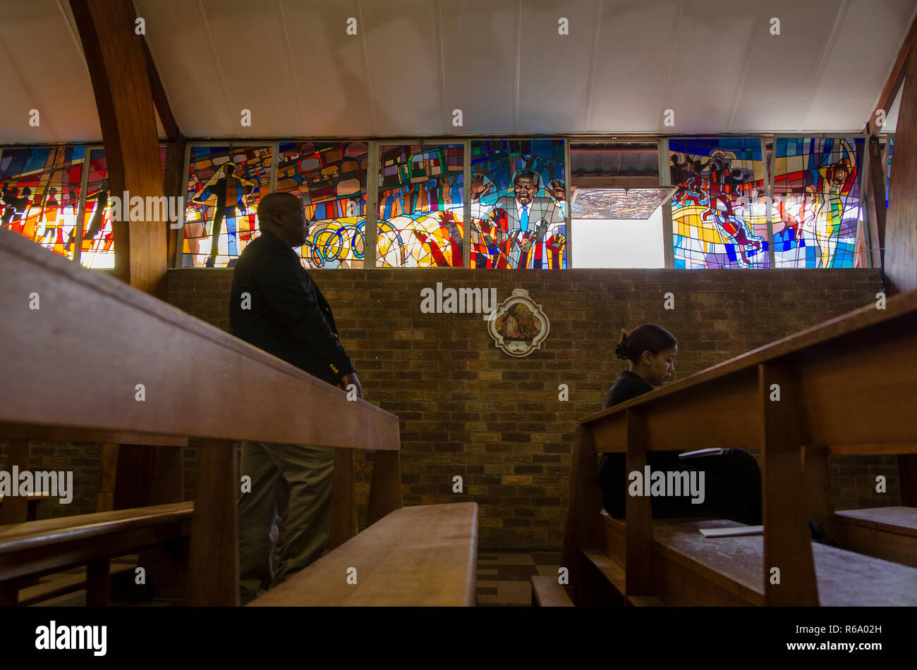 Mourners are seen in front of a stained glass window depicting Nelson Mandela as they arrive for a church service for the former South African President at Regina Mundi, Soweto, Sunday, December 8, 2013. The elder statesman died Thursday evening, December 5, 2013. PHOTO: EVA-LOTTA JANSSON Stock Photo