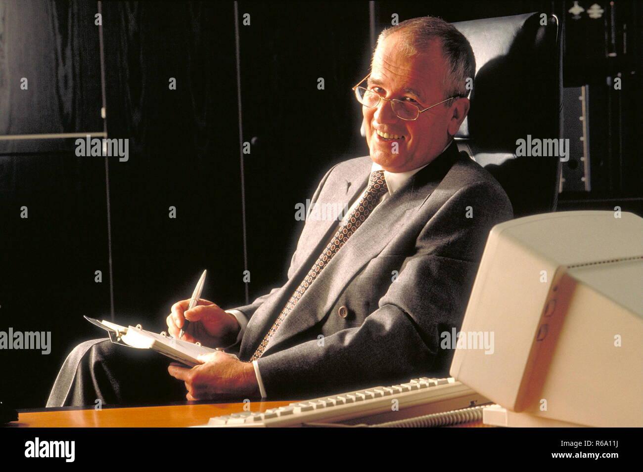 Portrait, Bueroszene, Manager, ca. 60 Jahre, mit Kalender an seinem Arbeitsplatz in seinem Buero - Stock Image