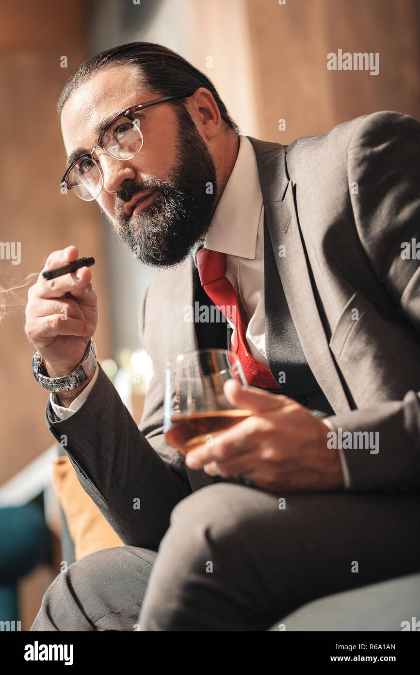 Bearded businessman sitting in comfy armchair smoking and drinking - Stock Image