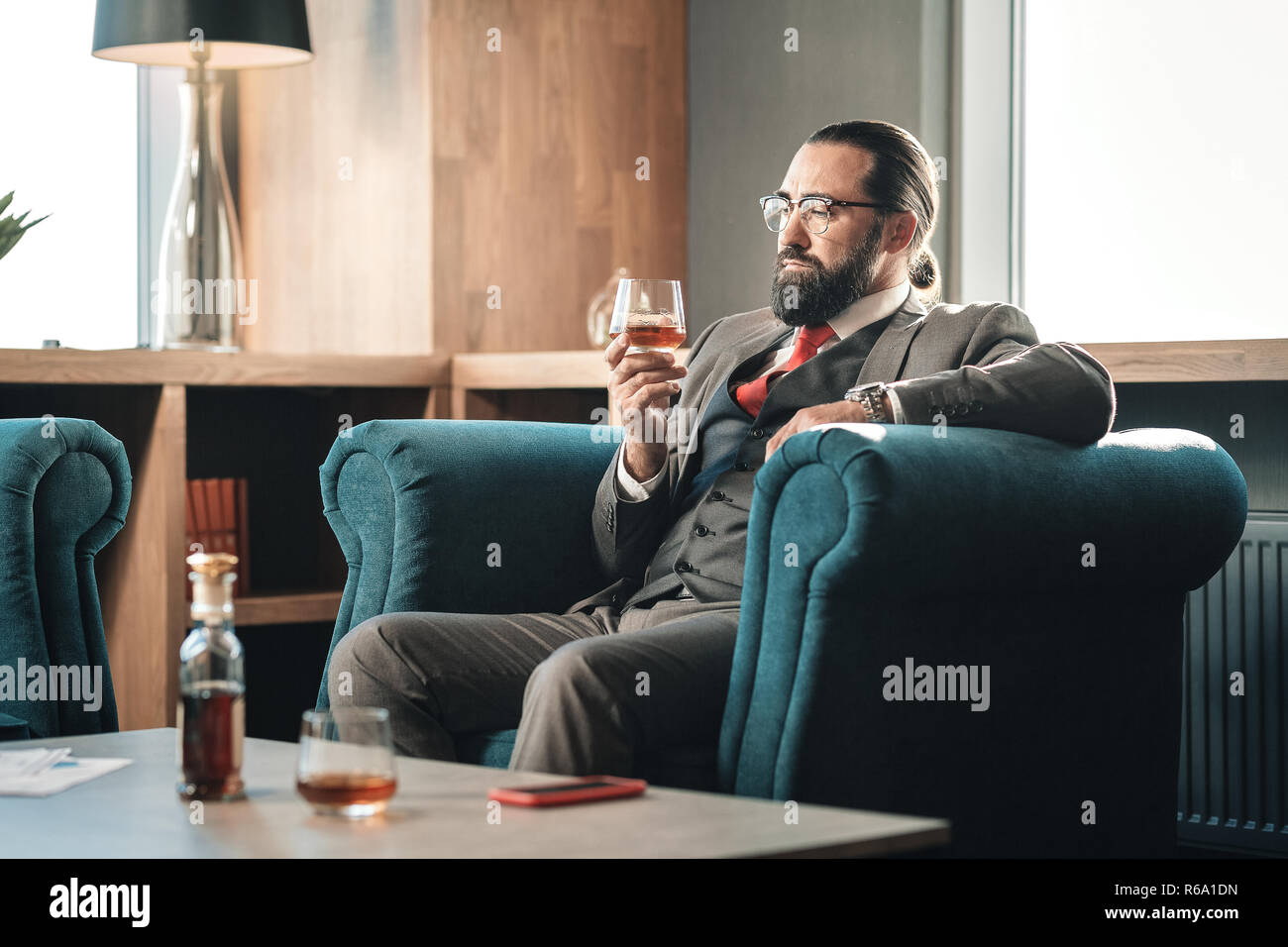 Experienced advocate drinking some whisky while feeling concerned - Stock Image