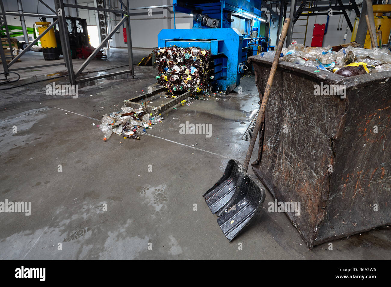 Modern waste sorting and recycling plant, hydraulic press makes wired bale from pressed PET bottles for processing and reuse of plastic. Concept of en Stock Photo