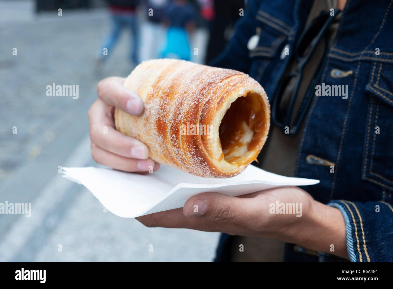 closeup of a yougn caucasian man eating a trdelnik, a typical spit cake, in the old town of Prague, Czech Republic - Stock Image