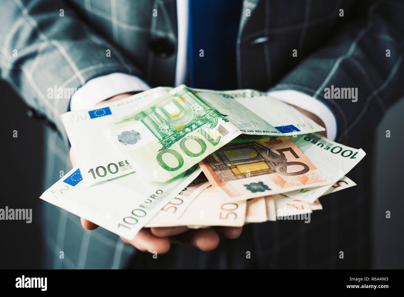 closeup of a young caucasian businessman, wearing an elegant gray suit, with a handful of euro banknotes in his hands - Stock Image