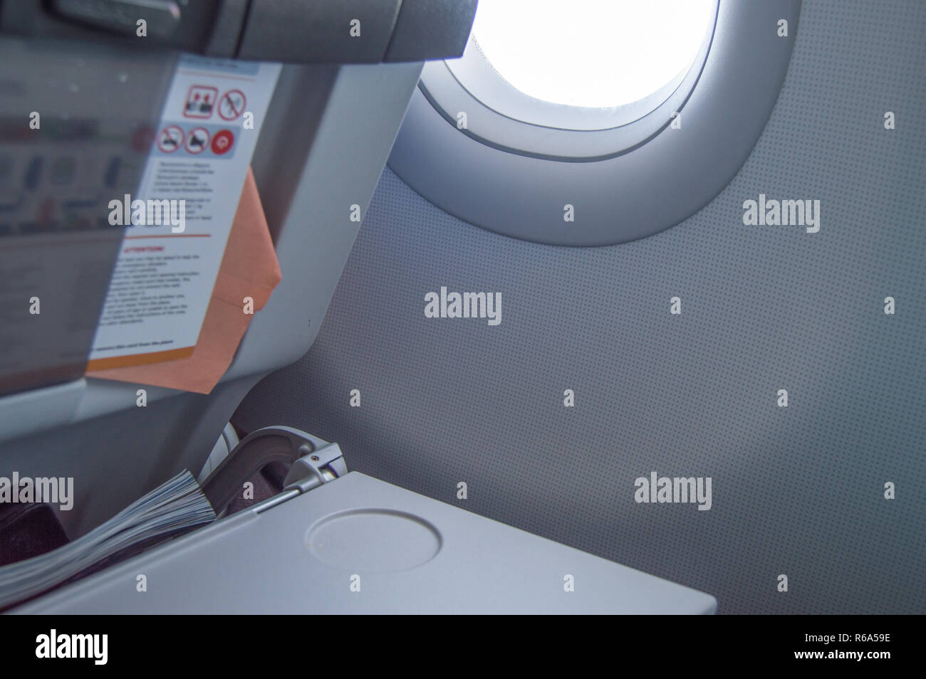 Folding table, flight instructions, magazine in the front seat, porthole, concept of flights and travel - Stock Image