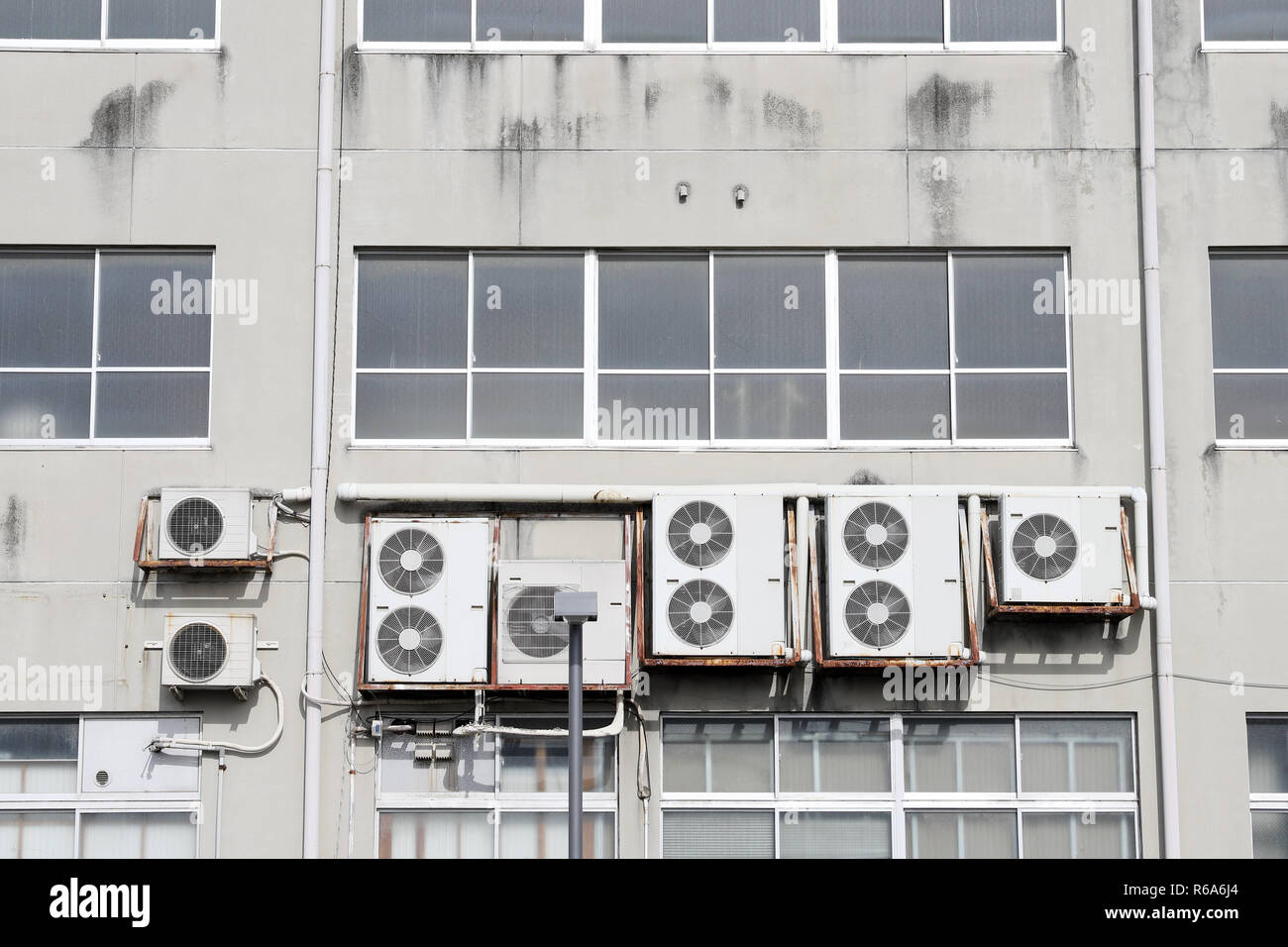 Air conditioners on the wall, Many compressor airs are hanging on a wall - Stock Image