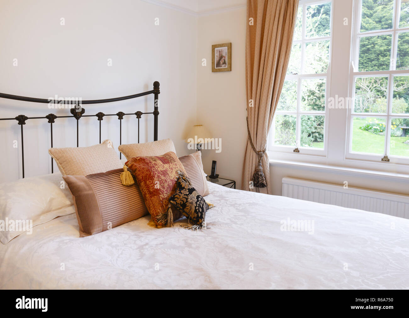Bedroom interior in a traditional style English house with luxury soft furnishing - Stock Image