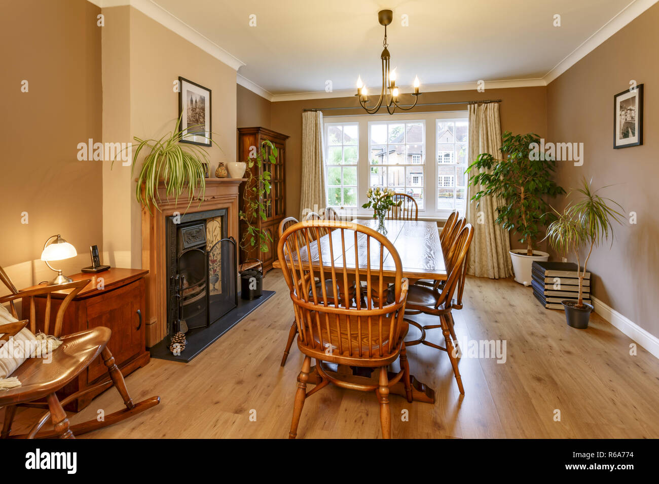 Traditional dining room interior with fireplace, wooden furniture, table and chairs - Stock Image