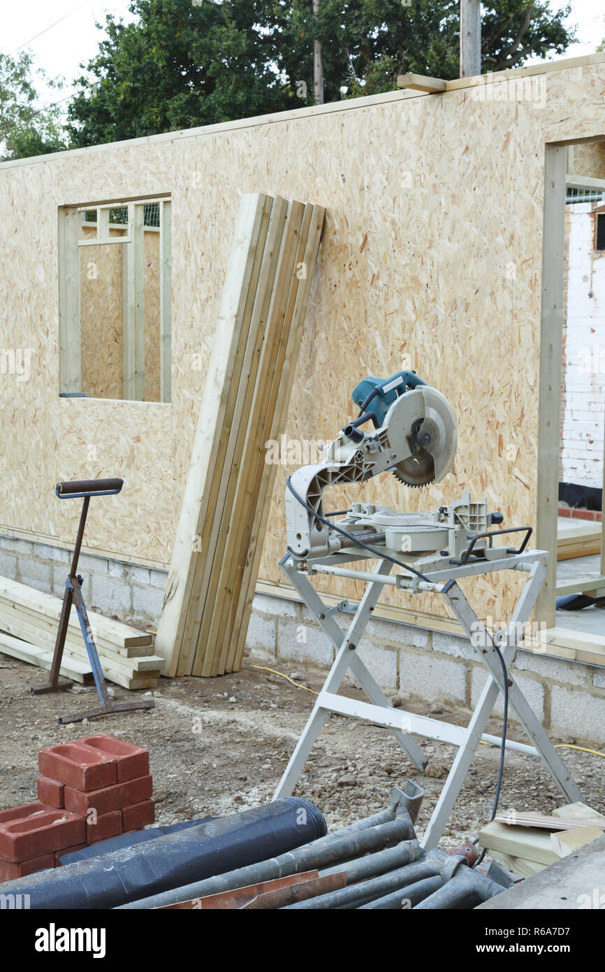 Carpenter's chop saw and timber with a timber framed house under construction in the background Stock Photo