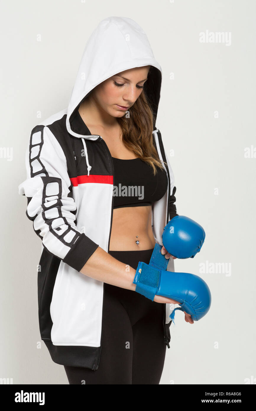 Young Woman Getting Ready For The Fight And Puts On Her Boxing Gloves - Stock Image