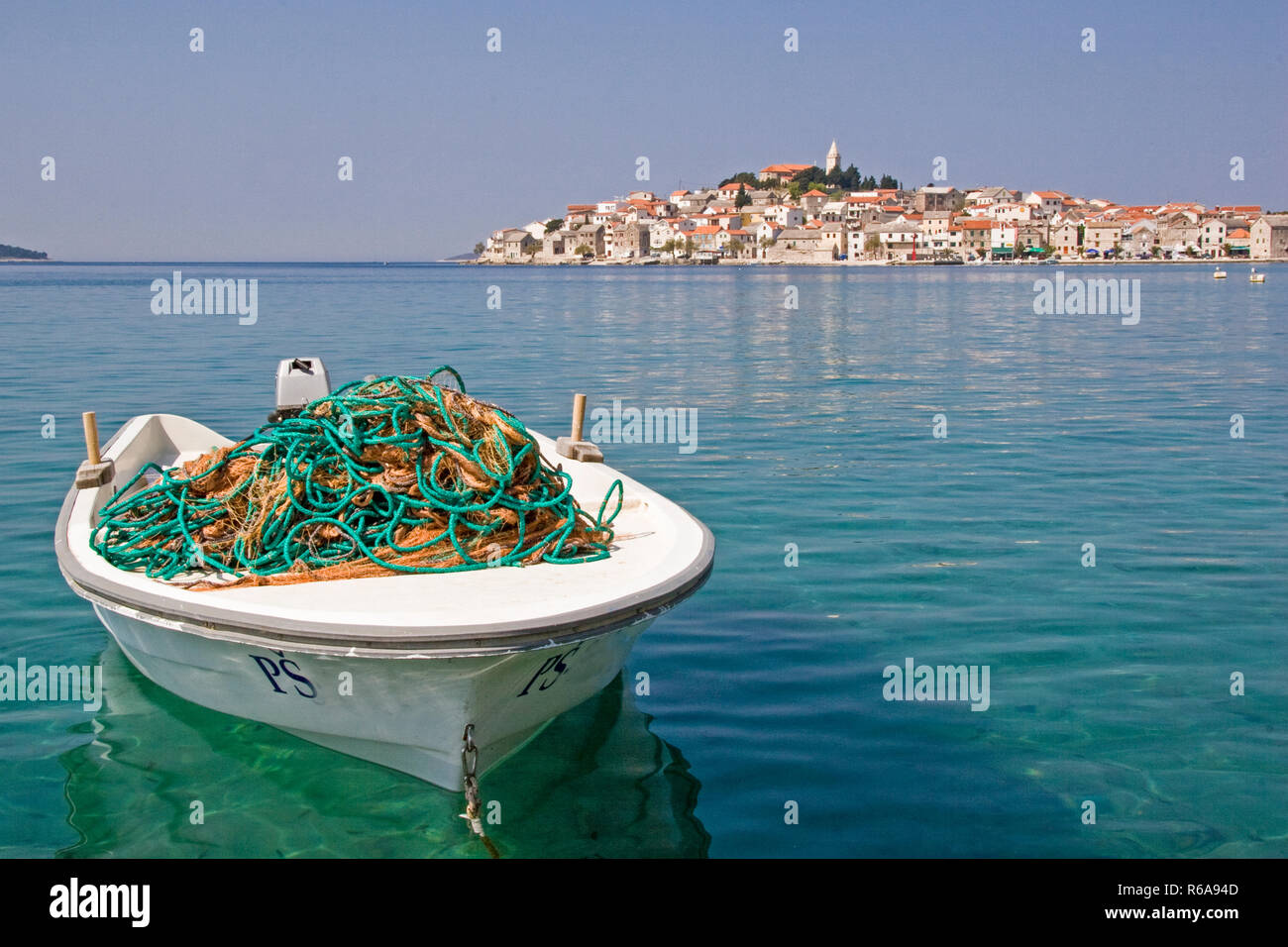 Fishing Boat In Front Of The Small Idyllic Fishing Village Primosten, Which Is Picturesquely Situated On A Peninsula And Often Referred To As The Pear - Stock Image
