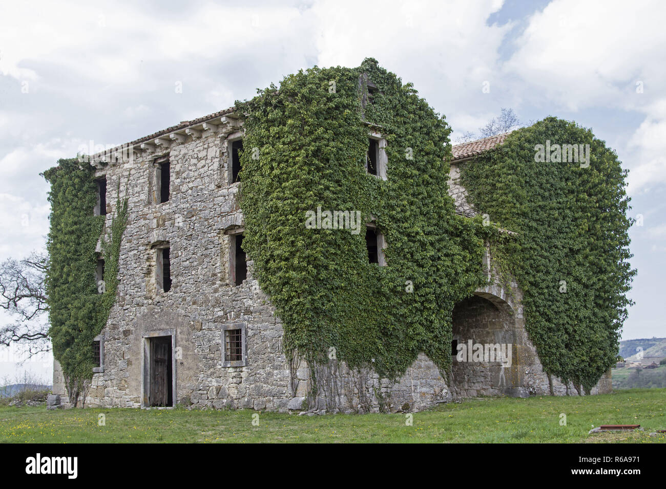Abandoned And Dilapidated Houses Idyllically Overgrown With Plants Characterize The Idyllic Landscape - Stock Image